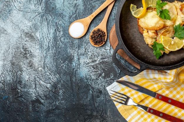 Vista superior de peixe frito na frigideira com especiarias de limão e salsa em colheres de madeira, garfo e faca no fundo cinza