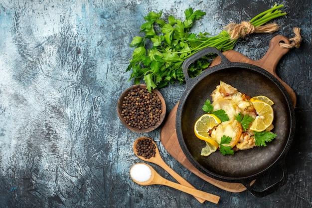 Vista superior de peixe frito na frigideira com especiarias de limão e salsa em colheres de madeira.