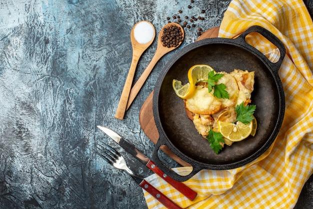 Vista superior de peixe frito na frigideira com limão e salsa, sal e pimenta em colheres de madeira