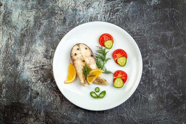 Vista superior de peixes crus e alimentos frescos com pimenta em um prato branco na superfície cinza do gelo