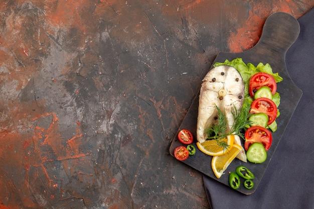 Vista superior de peixes crus e alimentos frescos com pimenta em uma tábua de corte preta em uma toalha de cor escura em uma superfície de cor mista