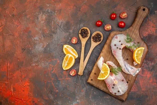 Vista superior de peixes crus e pimenta na tábua de corte de madeira, fatias de limão, tomates na superfície da mistura de cores