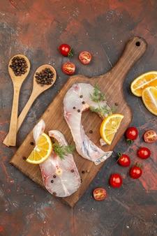 Vista superior de peixes crus e pimenta na tábua de corte de madeira, fatias de limão, tomates na superfície da mistura