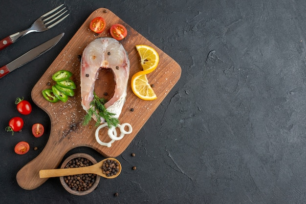Vista superior de peixes crus e vegetais frescos picados, fatias de limão, especiarias em uma placa de madeira talheres colocados do lado direito em uma superfície preta estressada