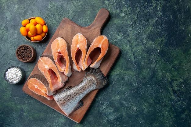 Vista superior de peixes crus frescos em uma tábua de madeira e pimentas de kumquats na mesa de cores escuras