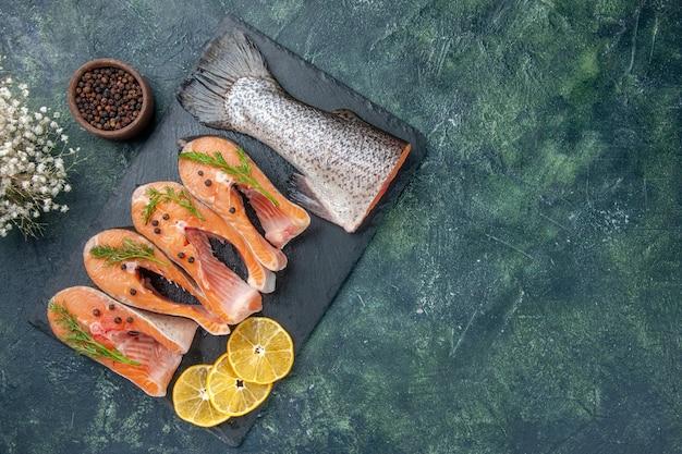 Vista superior de peixes crus frescos, verdes, pimenta e rodelas de limão na bandeja de cor escura da tabela de cores misturadas