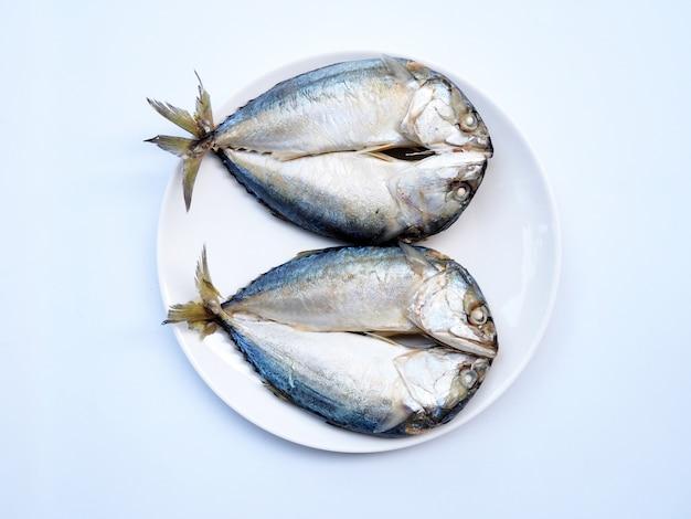Vista superior de peixes de cavala dupla, braquitoma rastrelliger na chapa branca para cozinhar isolado.