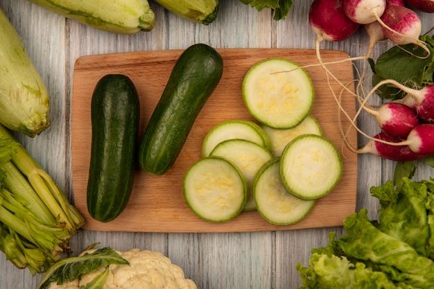 Vista superior de pepinos com poucas calorias em uma placa de cozinha de madeira com abobrinhas e aipo rabanetes isolados em uma superfície de madeira cinza