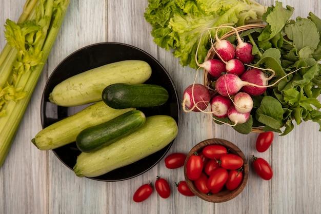 Vista superior de pepinos e abobrinhas orgânicas em um prato com tomates em uma tigela de madeira com rabanetes em um balde com tomate alface e aipo isolado em uma superfície cinza de madeira