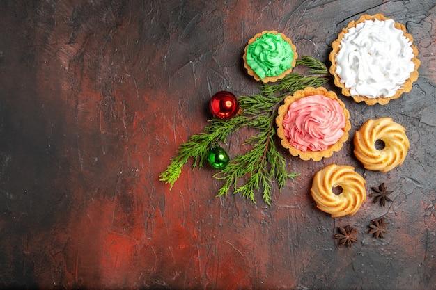 Vista superior de pequenas tortas, biscoitos, anis estrelados, brinquedos para árvores de natal na superfície vermelha escura