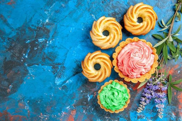 Vista superior de pequenas tortas com flores roxas de creme de pastelaria rosa e verde na superfície azul