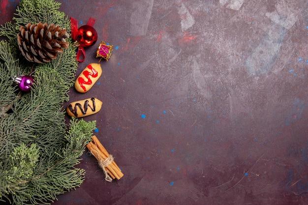 Vista superior de pequenos biscoitos com árvore e cones no preto