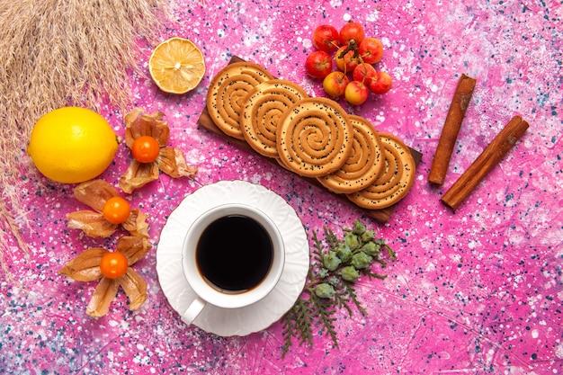 Vista superior de pequenos biscoitos deliciosos com chá de limão e canela na superfície rosa claro
