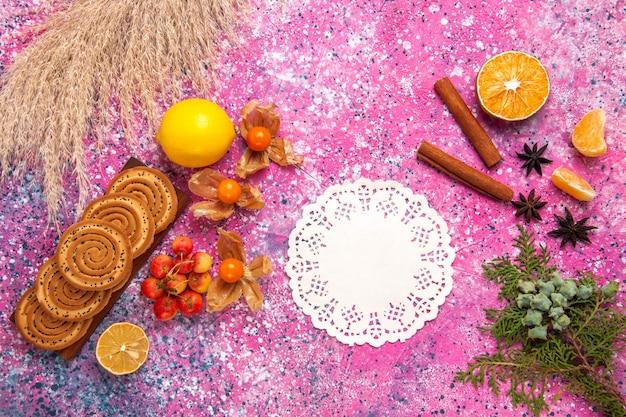 Vista superior de pequenos biscoitos deliciosos com limão e canela na superfície rosa claro