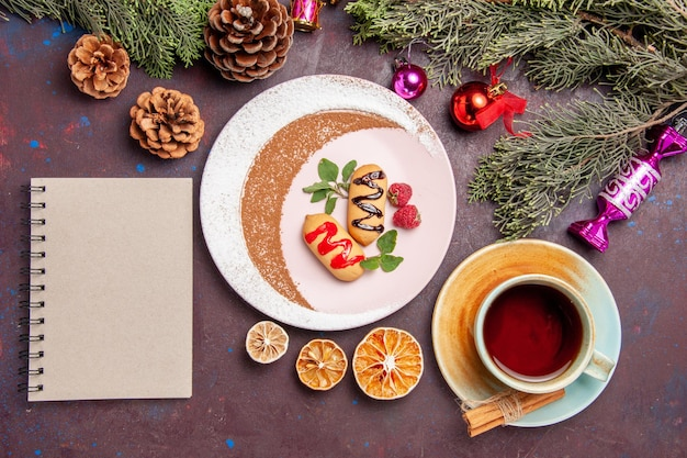 Vista superior de pequenos biscoitos doces com uma xícara de chá no preto