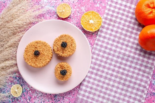 Vista superior de pequenos bolos com frutas na superfície rosa