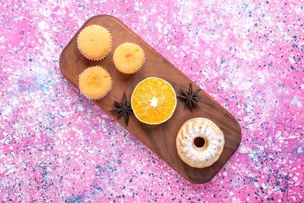 Vista superior de pequenos bolos com uma fatia de laranja na superfície rosa