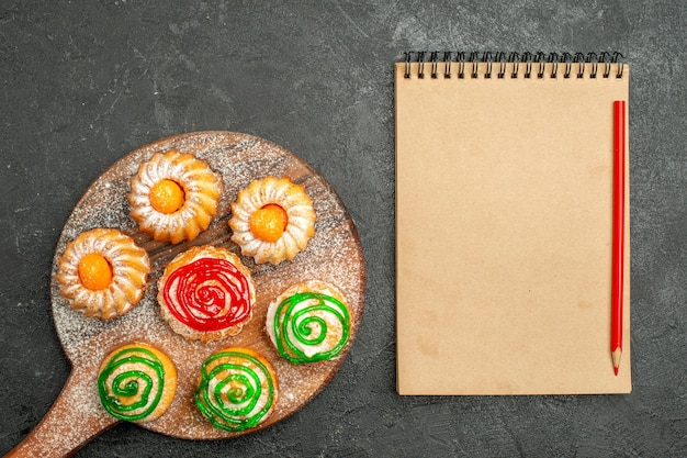Vista superior de pequenos bolos deliciosos com bloco de notas preto