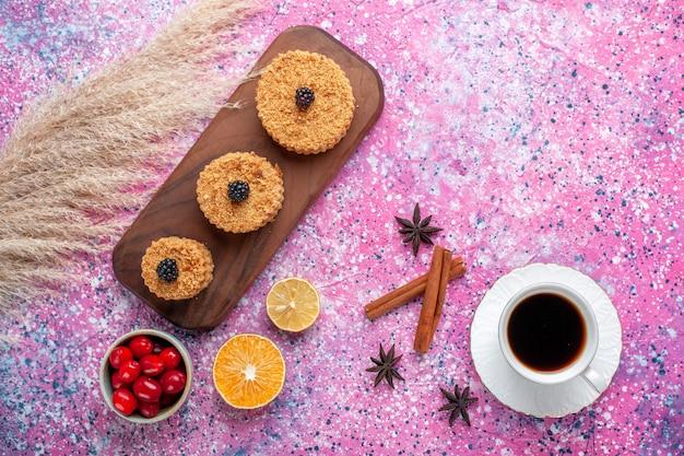 Vista superior de pequenos bolos deliciosos com canela e xícara de chá na superfície rosa claro