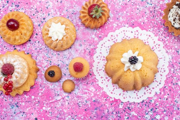 Vista superior de pequenos bolos deliciosos com creme e frutas vermelhas