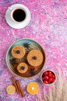 Vista superior de pequenos bolos deliciosos com dogwoods e chá na superfície rosa claro