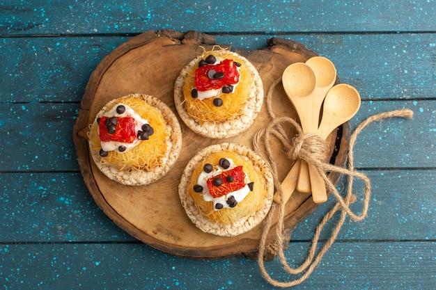 Vista superior de pequenos bolos deliciosos com frutas na placa de madeira marrom e superfície azul