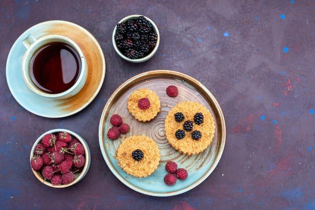 Vista superior de pequenos bolos doces e deliciosos com frutas frescas e chá na superfície escura