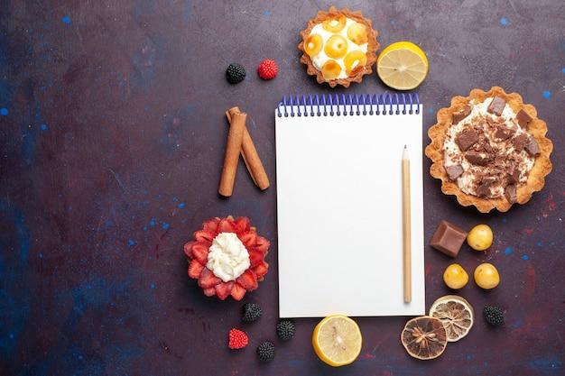 Vista superior de pequenos bolos saborosos com creme, juntamente com doces e bloco de notas de chá na superfície escura