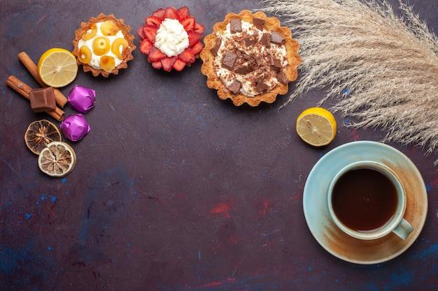 Vista superior de pequenos bolos saborosos com creme, juntamente com doces e chá na superfície escura