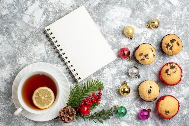 Vista superior de pequenos cupcakes e acessórios de decoração ramos de abeto coníferas cone uma xícara de chá preto ao lado de um caderno fechado na superfície do gelo