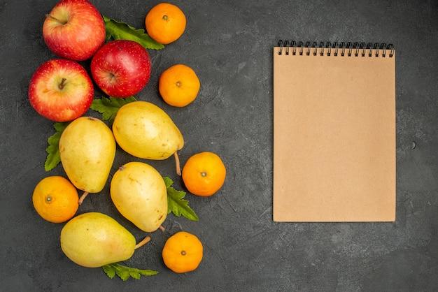 Vista superior de peras doces frescas com tangerinas e maçãs em fundo cinza