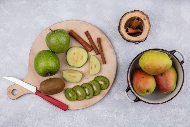 Vista superior de peras em uma panela com maçãs verdes canela e kiwi com uma faca em um suporte sobre fundo branco