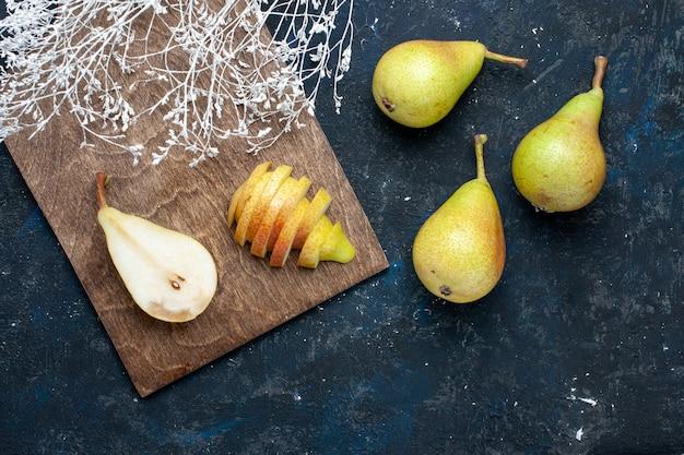 Vista superior de peras frescas inteiras fatiadas e doces na mesa escura, frutas frescas e saudáveis.