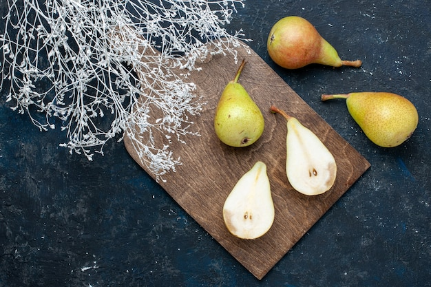 Vista superior de peras frescas maduras inteiras fatiadas e frutas doces em azul-escuro, frutas frescas maduras alimentos saudáveis