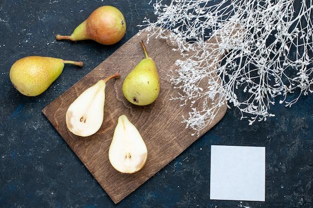 Vista superior de peras frescas maduras inteiras fatiadas e frutas doces em uma mesa azul-escura, frutas frescas maduras