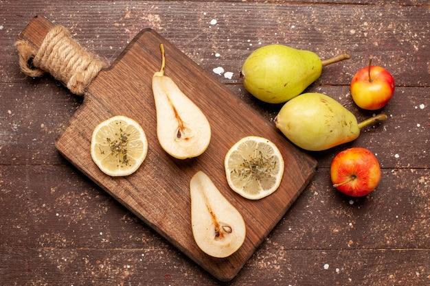Vista superior de peras frescas maduras no espaço marrom