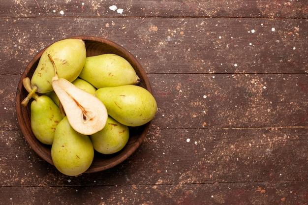 Vista superior de peras frescas maduras, verdes e suculentas no espaço marrom