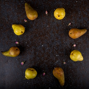 Vista superior de peras maduras frescas, dispostas em círculo sobre fundo preto, com espaço de cópia