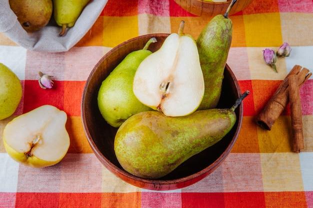 Vista superior de peras maduras frescas e meia em uma tigela de madeira e paus de canela na manta