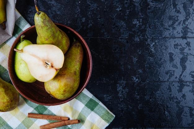 Vista superior de peras maduras frescas e meia em uma tigela de madeira e paus de canela no fundo preto de madeira com espaço de cópia