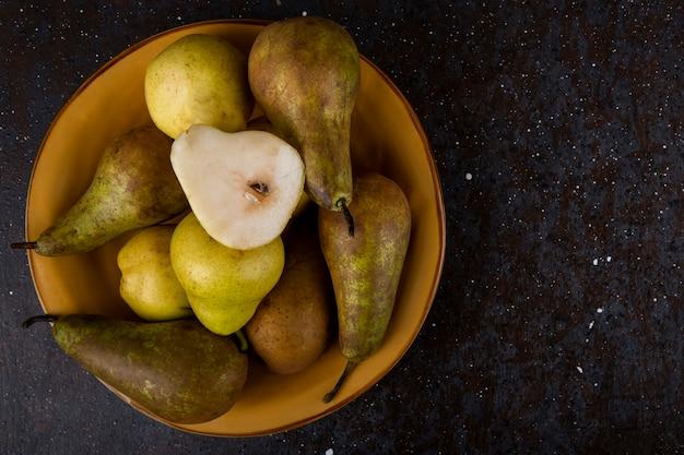 Vista superior de peras maduras frescas em um prato fundo preto