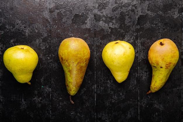 Vista superior de peras maduras frescas em uma linha em fundo preto de madeira