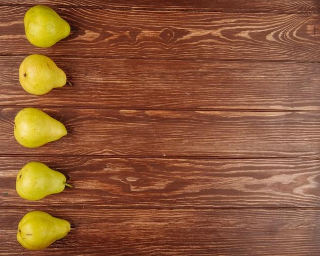 Vista superior de peras maduras frescas em uma linha em um fundo de madeira com espaço de cópia