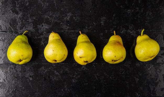 Vista superior de peras maduras frescas em uma linha no fundo preto de madeira com espaço de cópia