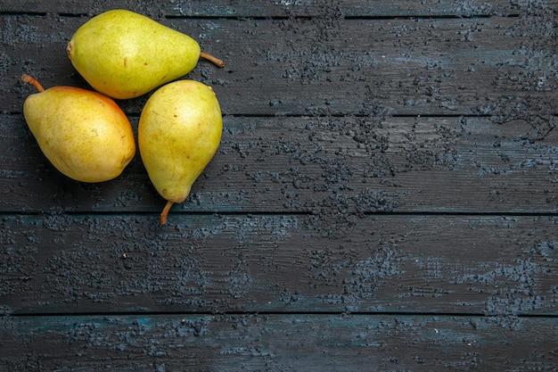 Vista superior de peras verdes na mesa três peras verdes maduras no lado esquerdo da mesa de madeira