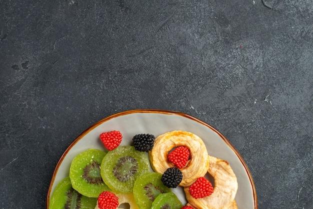 Vista superior de perto anéis de abacaxi secos com kiwis secos e maçãs na parede cinza-escuro frutas passas secas doces açúcar doce