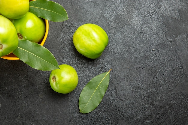 Vista superior de perto balde de tomates verdes e folhas de louro e tomates na mesa escura com espaço de cópia