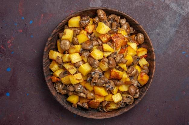 Vista superior de perto batatas com cogumelos batatas fritas com cogumelos fritos em uma tigela de madeira em um fundo escuro