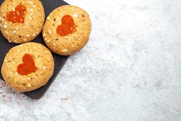 Vista superior de perto biscoitos de açúcar deliciosos doces para chá em um fundo branco torta biscoito biscoito doce bolo doce