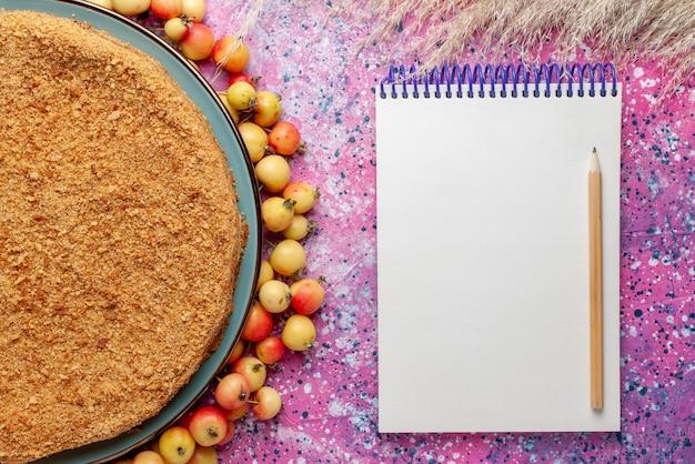 Vista superior de perto bolo redondo delicioso dentro do prato com bloco de notas forrado de cerejas doces na mesa rosa brilhante torta de bolo biscoito doce assar açúcar